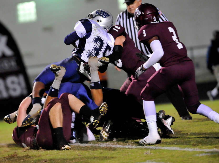 Mustang #35, Abear Simien, left, holds the ball tight as defenders try to hold him.  The Silsbee High School Tigers hosted the West Orange-Stark High School Mustangs Friday night November 9, 2012 at Tiger stadium in Silsbee. This is a District 21-3A game, and both teams were undefeated in district play going into the game.At the half, the Mustangs are up 13-12. Dave Ryan/The Enterprise Photo: Dave Ryan, Dave Ryan/The Enterprise