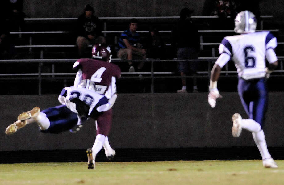 Tiger #4, Coy Bird,scores a touchdown while Mustang #29,  Quinton Tezeno, tries to catch him by diving for his feet.  The Silsbee High School Tigers hosted the West Orange-Stark High School Mustangs Friday night November 9, 2012 at Tiger stadium in Silsbee. This is a District 21-3A game, and both teams were undefeated in district play going into the game.At the half, the Mustangs are up 13-12.	 Dave Ryan/The Enterprise Photo: Dave Ryan, Dave Ryan/The Enterprise
