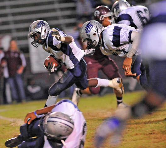 Mustang #9, Brandon Gore, left, breaks through the Tiger defense to gain some ground. The Silsbee High School Tigers hosted the West Orange-Stark High School Mustangs Friday night November 9, 2012 at Tiger stadium in Silsbee. This is a District 21-3A game, and both teams were undefeated in district play going into the game.At the half, the Mustangs are up 13-12.	 Dave Ryan/The Enterprise Photo: Dave Ryan, Dave Ryan/The Enterprise