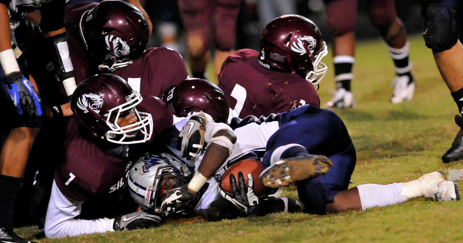 Mustang #9, Brandon Gore, center, is brought down by several Tiger defenders including #7, Jordan Holmes, and #3, Kendrick Scott, right.  The Silsbee High School Tigers hosted the West Orange-Stark High School Mustangs Friday night November 9, 2012 at Tiger stadium in Silsbee. This is a District 21-3A game, and both teams were undefeated in district play going into the game.At the half, the Mustangs are up 13-12.	 Dave Ryan/The Enterprise Photo: Dave Ryan, Dave Ryan/The Enterprise