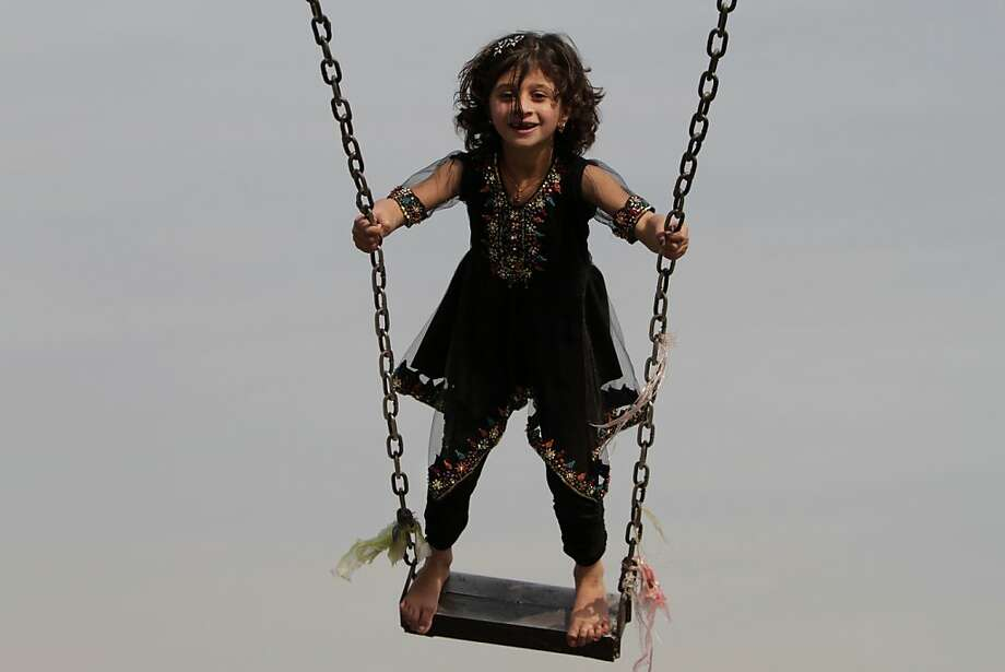 That daring young girl on the flying trapeze:A little acrobat rides a swing in an amusement park in Jalalabad, Afghanistan. Photo: Rahmat Gul, Associated Press