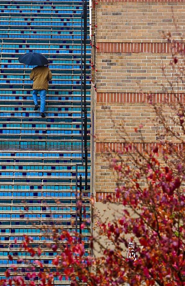 A man climbs a stair on a cold and rainy day in Kansas City, Mo. Photo: Allison Long, Associated Press