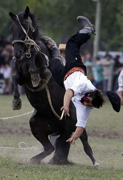 Ouch-o, gaucho: A bucking bronc throws its rider during a Tradition Day rodeo in San Antonio