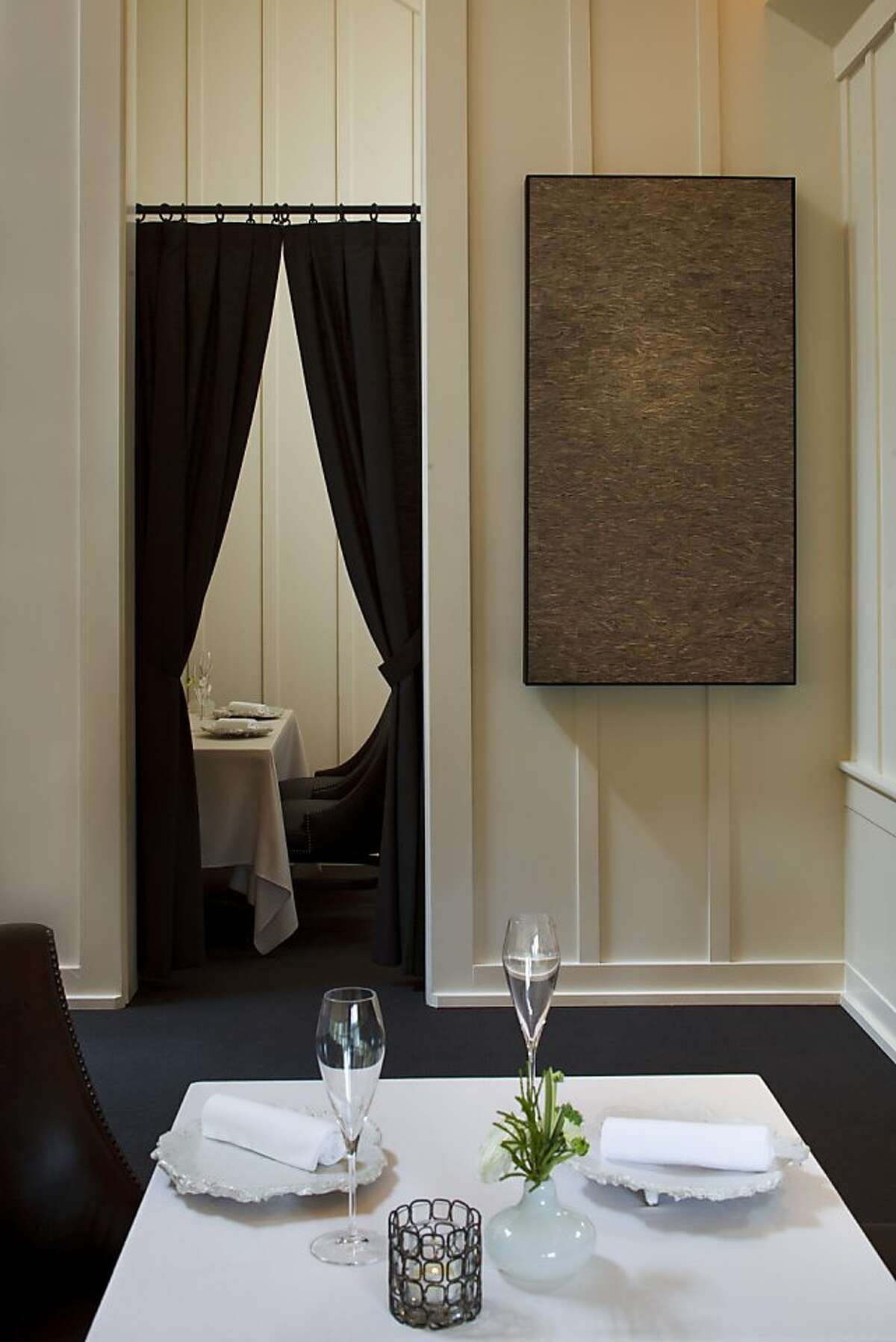 Artwork by Jonah Ward, known as wasp nest, hangs in the main dining room of the Meadowood Resort dining room. The small, private dining area can be seen through the parted curtains.