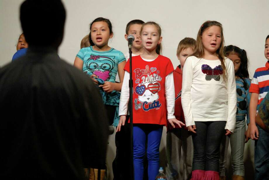Third grade students Madeline Olivia, Caroline Sobieszczak and Magda Chrzanowska from Springdale School in Stamford, Conn. sing at concert for Veteran's Day on Monday November 12, 2012. Photo: Dru Nadler / Stamford Advocate Freelance