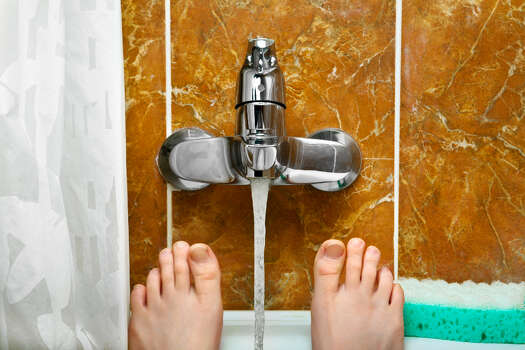 Reduce the level of the water being used in a bathtub by one or two inches if a shower is not available. Photo: Tarasov_vl - Fotolia / tarasov_vl - Fotolia