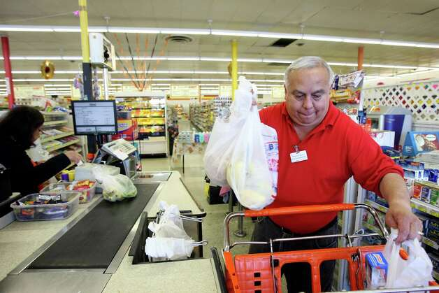 Richard Garcia places Gloria Martinez's groceries in a cart at Arlen's Market, formerly Handy Andy, on the city's West Side. Photo: Helen L. Montoya, San Antonio Express-News / ©SAN ANTONIO EXPRESS-NEWS