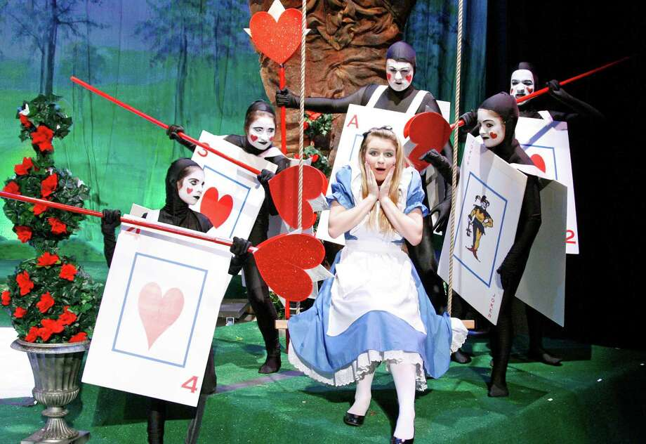 "Alice (played by Elizabeth Koennecke) is frightened by a pack of cards, from left, Margot Weiss, Lauren Peet, Pete Thunem, Berlin Charles and Melissa Calabro during the production of ""Alice in Wonderland,"" which will be staged at New Canaan High School on Nov. 16 and 17. Photo: Contributed"