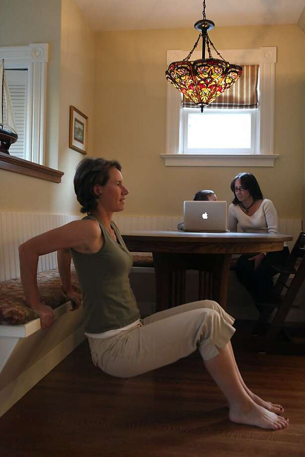 Kristen Strellis demonstrates a triceps dip in her kitchen. Photo: Liz Hafalia, The Chronicle