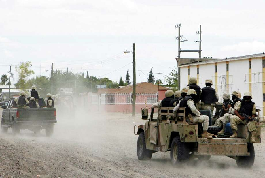 Mexican Army soldiers patrol the streets of Ojinaga, on Mexico's border with U.S., Wednesday, July 24, 2008. Ojinaga's citizens protested a day earlier against abuses by Mexican soldiers sent to crack down drug trafficking. Mexico's National Human Rights Commission says it has documented more than 600 cases of abuse since Calderon sent troops on anti-narcotics missions throughout Mexico beginning in 2006. (AP Photo/Guillermo Arias) Photo: Guillermo Arias, ASSOCIATED PRESS / AP2008