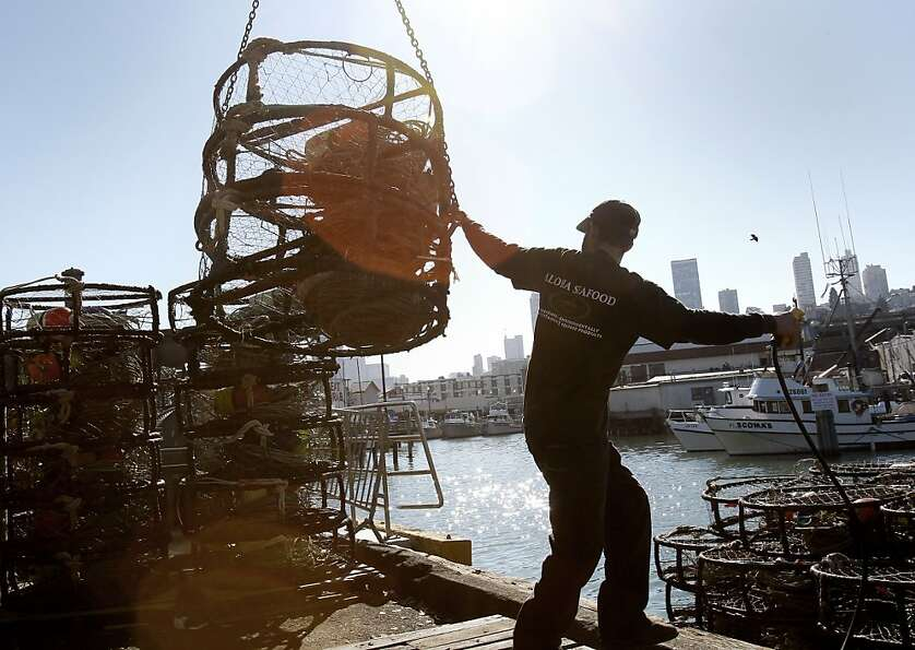 A fisherman is among many hustling to load crab pots and ready boats on Pier 45 in San Francisco.