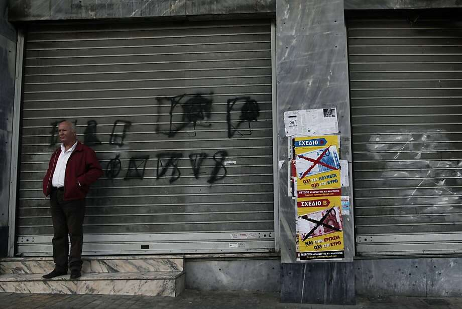 "Posters reading ""Yes to Work, No to the Euro"" are stuck on a wall next to a shuttered shop in Athens. Photo: Petros Giannakouris, Associated Press"