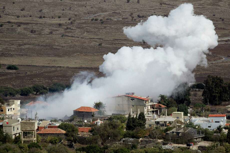 Smoke rises after shells explode Monday in the Syrian village of Bariqa, in the Golan Heights near the border with Israel. An Israeli tank hit a Syrian armored vehicle after a mortar shell landed on Israeli-held territory. Photo: Ariel Schalit, STF / AP