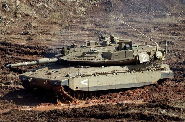 "An Israeli tank in a firing position in the Israeli-controlled Golan Heights overlooking the Syrian village of Bariqa, Monday, Nov. 12, 2012. The Israeli military says ""Syrian mobile artillery"" was hit after responding to stray mortar fire from its northern neighbor. The incident marked the second straight day that Israel has responded to fire from Syria that does not appear to be aimed at Israeli targets, nonetheless Israel has promised a tough response if the fire continues. (AP Photo/Ariel Schalit) Photo: Ariel Schalit"