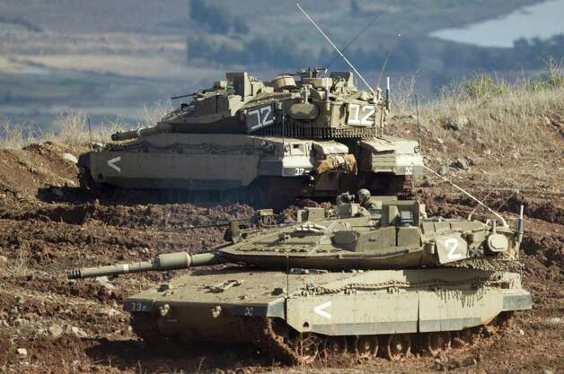 "Israeli tanks, one in position, the other getting into a firing position in the Israeli-controlled Golan Heights overlooking the Syrian village of Bariqa, Monday, Nov. 12, 2012. The Israeli military says ""Syrian mobile artillery"" was hit after responding to stray mortar fire from its northern neighbor. The incident marked the second straight day that Israel has responded to fire from Syria that does not appear to be aimed at Israeli targets, nonetheless Israel has promised a tough response if the fire continues. (AP Photo/Ariel Schalit) Photo: Ariel Schalit"