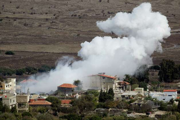 "Smoke rises after shells exploded in the Syrian village of Bariqa, near the Israeli-Syrian border, near Alonei Habashan in the  Golan Heights, Monday, Nov. 12, 2012. An Israeli tank scored a ""direct hit"" Monday on a Syrian armored vehicle after a mortar shell landed on Israeli-held territory, the military said, in the first direct confrontation between the countries since the Syrian uprising broke out, sharpening fears that Israel could be drawn into the civil war next door. (AP Photo/Ariel Schalit) Photo: Ariel Schalit"