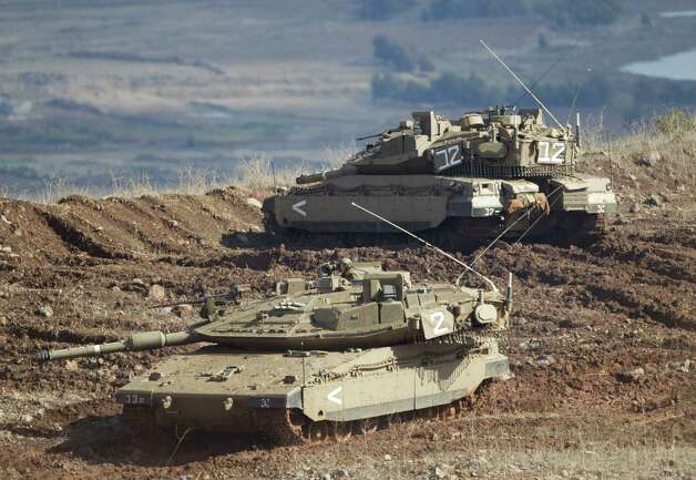 "Israeli tanks, one in position, the other getting into a firing position in the Israeli-controlled Golan Heights overlooking the Syrian village of Bariqa, Monday, Nov. 12, 2000. The Israeli military says ""Syrian mobile artillery"" was hit after responding to stray mortar fire from its northern neighbor. The incident marked the second straight day that Israel has responded to fire from Syria that does not appear to be aimed at Israeli targets, nonetheless Israel has promised a tough response if the fire continues. (AP Photo/Ariel Schalit) Photo: Ariel Schalit"