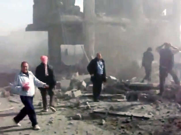 This image taken from video obtained from Shaam News Network, which has been authenticated based on its contents and an Associated Press journalist who saw a plane bomb an area around the Syrian-Turkish border town of Ras al-Ayn, shows Syrians inspecting the damage and looking for victims moments after an airstrike by Syrian warplanes in Ras al-Ayn, Syria, Monday, Nov. 12, 2012. (AP Photo/Shaam News Network via AP video) Photo: Anonymous