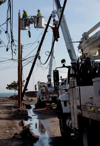 A crew with Salt River Project of Arizona (SRP) works on replacing a pole in the Belle Harbor neighborhood of the borough of Queens, New York, Monday, Nov.12, 2012, in the wake of Superstorm Sandy. SRP is one of several out of the region utility companies aiding local utilities. (AP Photo/Craig Ruttle) Photo: Craig Ruttle