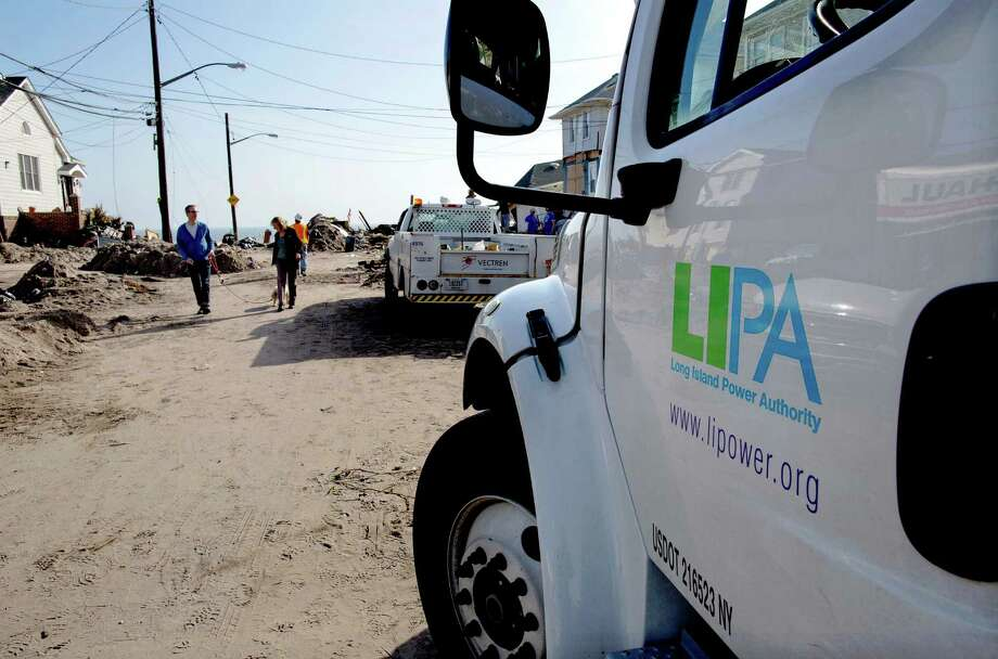 A Long Island Power Authority (LIPA) truck is seen in the Belle Harbor neighborhood of the borough of Queens, New York, Monday, Nov.12, 2012, in the wake of Superstorm Sandy.  More than 70,000 customers of Long Island Power Authority in New York were without electricity Monday, two weeks after Superstorm Sandy struck. (AP Photo/Craig Ruttle) Photo: Craig Ruttle