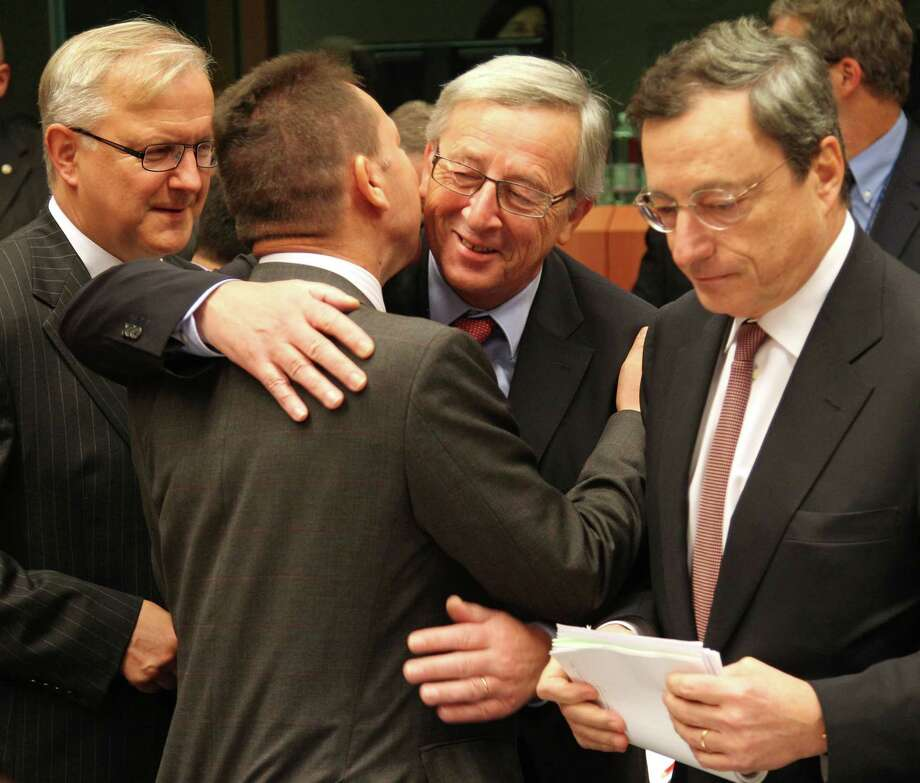 "Luxembourg's Prime Minister and chairman of the Eurogroup Jean-Claude Juncker, second right, greets Greek Finance Minister Yannis Stournaras, second left, as European Commissioner for Economic and Monetary Affairs Olli Rehn, left, and President of the European Central Bank Mario Draghi, right, look on, during the Eurogroup finance ministers meeting in Brussels, Monday, Nov, 12, 2012. Greece's international lenders have prepared a ""positive"" report on the country's reform efforts, a crucial step in its efforts to secure the next installment of its bailout loan, the head the of group of finance ministers from the 17 euro countries said Monday. (AP Photo/Yves Logghe) Photo: Yves Logghe"