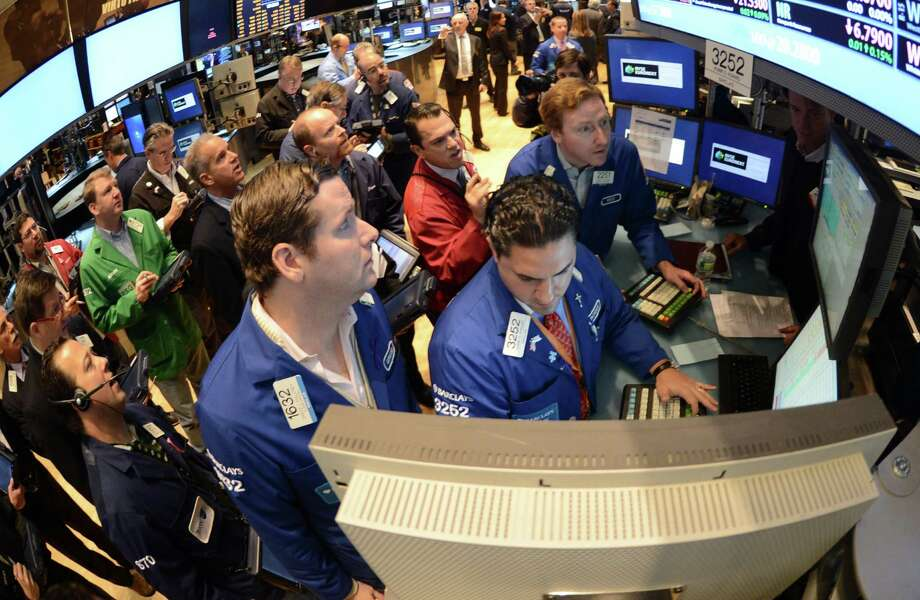 FILE - In this Thursday, Nov. 8, 2012, file photo, Gregg Maloney, left, and Ronnie Howard, center, both of Barclays, direct trading on the floor of the New York Stock Exchange, in New York  U.S. stocks eked out the tiniest of gains on Monday Nov. 12, 2012, small comfort after worries about the fiscal cliff sent the market plunging last week.  (AP Photo/Henny Ray Abrams) Photo: Henny Ray Abrams