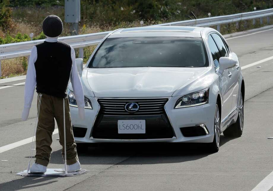 Toyota's Lexus LS stops automatically in front of a dummy during a Toyota Motor Corp. demonstration of the pre-collision system (PCS) at its Higashi-Fuji Technical Center in Susono, southwest of Tokyo, Monday, Nov. 12, 2012. The PCS, one of the automaker's pedestrian accident countermeasures, watches out for pedestrians to avoid collisions with them. (AP Photo/Koji Sasahara) Photo: Koji Sasahara