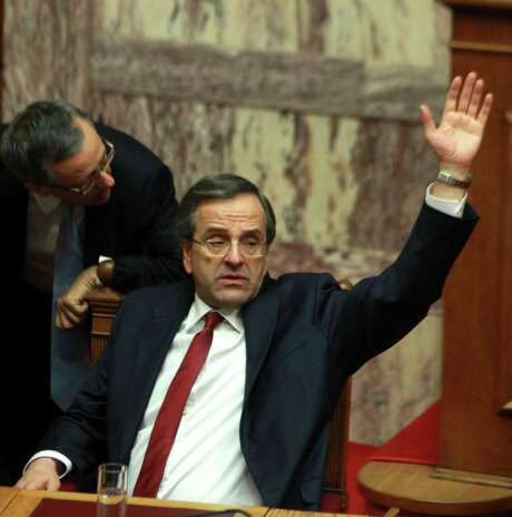 Greece's Prime Minister Antonis Samaras votes for the country's 2013 budget in Athens, Monday, Nov. 12, 2012. Greek lawmakers have approved the country's 2013 austerity budget, an essential step in Greece's efforts to persuade its international creditors to unblock a vital rescue loan installment without which the country will go bankrupt. (AP Photo/Thanassis Stavrakis) Photo: Thanassis Stavrakis, STF / AP