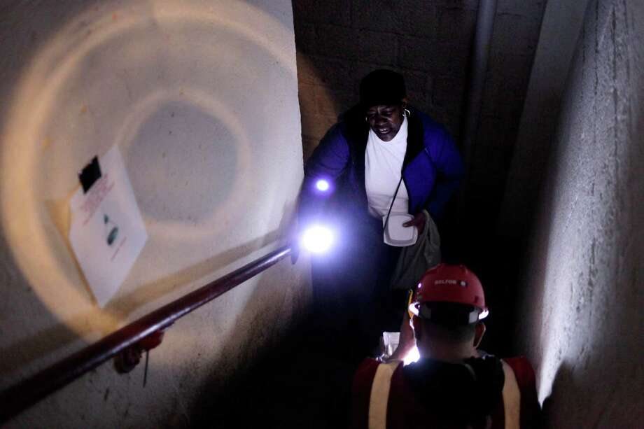 Guided by her flashlight, Karilyn Taylor trudges up 11 flights of stairs on Monday at the Red Hook Houses in the Red Hook section of Brooklyn, N.Y. Photo: Seth Wenig, STF / AP