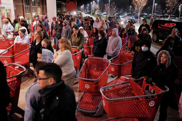 In this Friday, Nov. 25, 2011, file photo, a crowd of shoppers wait outside the Target store in Lisbon, Conn., before the store opens for Black Friday shopping at midnight.  This year, Target will open its doors at 9 p.m. on Thanksgiving, three hours earlier than a year ago, to kick off the holiday shopping season. (AP Photo/The Day) Photo: Associated Press / The Day