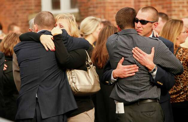 Mourners console each other following funeral services for Sgt. Brett E. Gornewicz, an Army Reservist who was killed Saturday by a roadside bomb in Afghanistan, at St. John the Baptist Church in Alden, Monday, Nov. 12, 2012. (AP Photo/Buffalo News, Derek Gee) Photo: Derek Gee