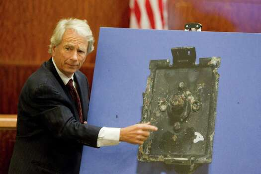 Defense attorney Mike DeGeurin shows a picture of a burned switch from the kitchen stove, which he argues was not the cause of the fatal fire. Photo: Johnny Hanson, Staff / © 2012  Houston Chronicle