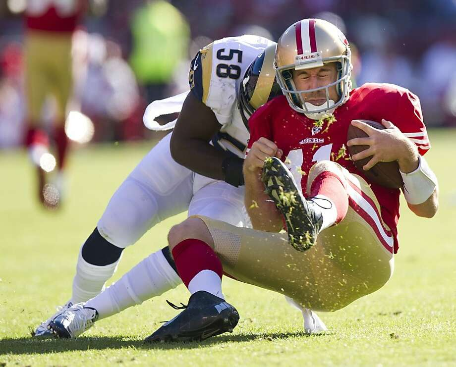 Alex Smith gets drilled by the Rams' Jo-Lonn Dunbar late in the first quarter Sunday. Smith would leave the game in the second quarter. Photo: Paul Kitagaki Jr., Associated Press