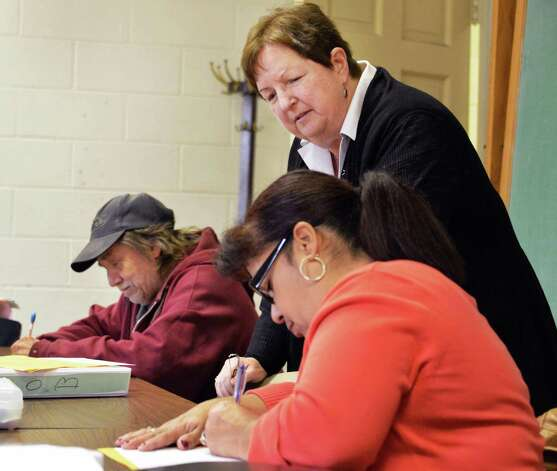 Teacher Judy Conine, top, with students Robert Snyder, left, and Lucy Vargas during her adult education class at the First Reformed Church in Hudson Tuesday Oct. 30, 2012. (John Carl D'Annibale / Times Union) Photo: John Carl D'Annibale / 00019890A