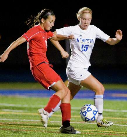Greenwich High School's Emma Christie tries to kick the ball before Newtown High School's Amy Martin gets to it in a Class LL game at Newtown. Monday, Nov. 12, 2012 Photo: Scott Mullin / The News-Times Freelance