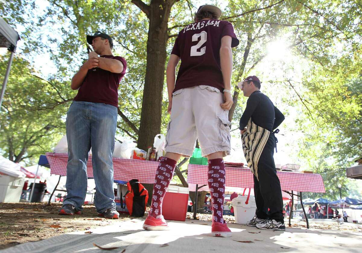 Sporting a Johnny Manziel No. 2 jersey, Brandon Neely, 17, of Waco, tailgates with Mitchell Long, a junior at Texas A&M, left, and Joe Calao of Waco before Saturday's game at Tuscaloosa, Ala., in which the Aggies upset Alabama 29-24.
