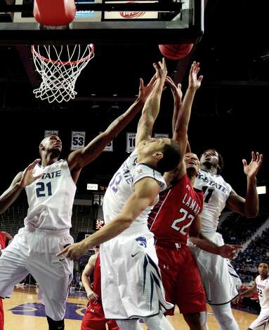 Kansas State's Angel Rodriguez (13), Jordan Henriquez (21) and Nino Williams (11) battle Lamar's Donley Minor (22) for a rebound during the second half of an NCAA college basketball game, Monday, Nov. 12, 2012, in Manhattan, Kan. Kansas State won 79-55. (AP Photo/Charlie Riedel) Photo: Charlie Riedel, STF / AP