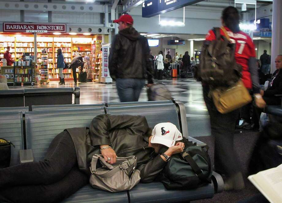 A Texans fan naps at a gate at O'Hare Airport on Monday in Chicago while waiting for a delayed flight home to Houston. Photo: Brett Coomer, Staff / © 2012  Houston Chronicle