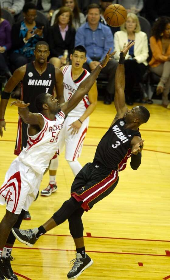 Rockets forward Patrick Patterson (54) attempts to defend a floater from Heat guard Dwayne Wade (3). (Billy Smith II / Houston Chronicle)