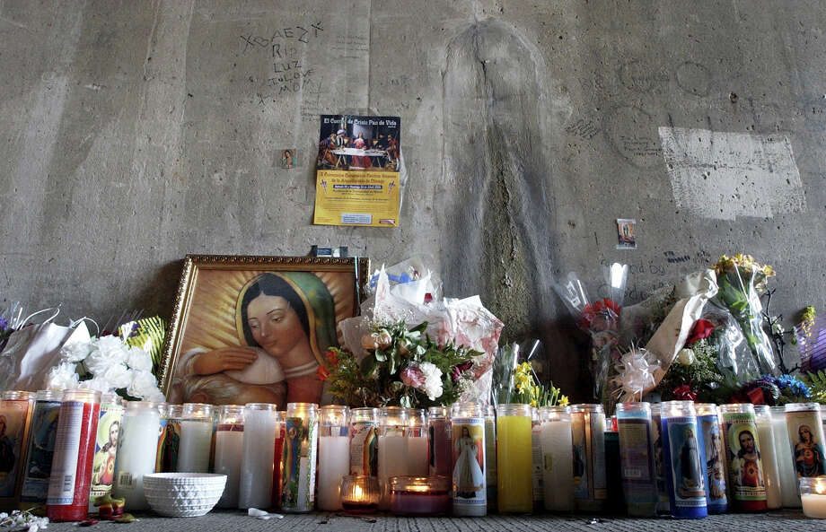 Candles, flowers and a painting of the Virgin Mary embracing John Paul II line the section of the Kennedy Expressway underpass on Chicago's northwest side Tuesday, April 19, 2005, where a yellow and white stain on a concrete wall that looks a lot like the Virgin Mary was discovered. Hundreds of people visited the site in the days after the discovery. Photo: CHARLES REX ARBOGAST, AP / AP