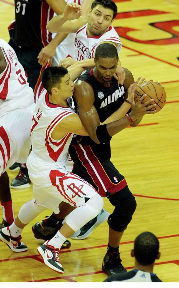 The Heat's Chris Bosh beats Jeremy Lin to a crucial rebound of a missed free throw, one of the clutch plays the defending champs made in the final minutes to avoid a loss. Photo: Billy Smith II, Staff / © 2012 Houston Chronicle