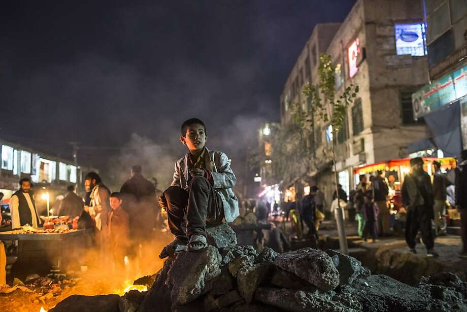 Curbside warmth:An Afghan boy sits by a fire burning in a street of the Old City of Kabul. Photo: Daniel Berehulak, Getty Images