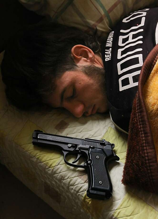"Syrian opposition fighter, Bazel Araj, sleeps next to his gun in the northern city of Aleppo on November 11, 2012. Araj, who is 19-years old, would prefer a peaceful revolution but he says ""the only way with President Bashar al-Assad is violence."" Photo: John Cantlie, AFP/Getty Images"