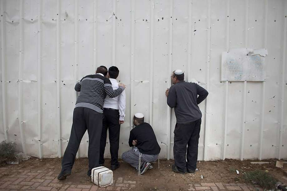 Israelis use holes in a fence to look into a factory after it was hit by a rocket launched from the Gaza Strip on November 12, 2012 in Netivot, Israel. Missile fire from Gaza has hit Israel for the fourth straight day. Photo: Uriel Sinai, Getty Images