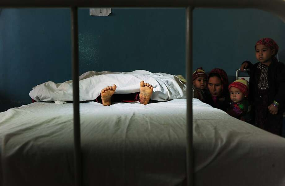 The family of a five year old Afghan girl, that was allegedly raped by a 22 year old man, looks on as she lies in a hospital bed in Kaldar district of Balk Province of Mazar-i-Sharif on November 12, 2012. The alleged rapist and neighbour was later detained by police. There is little sign that violence against women in Afghanistan is decreasing, despite billions of dollars of international aid which has poured into the country during the decade-long war.  Some 87 percent of Afghan women report having experienced physical, sexual or psychological violence or forced marriage, according to figures quoted in an October report by the British charity Oxfam. Photo: Qais Usyan, AFP/Getty Images