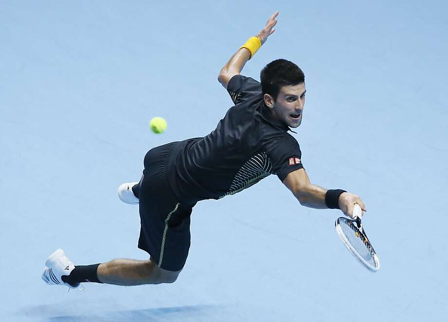 Noak Djokovic of Serbia dives as he attempts to play a return to Roger Federer of Switzerland during their ATP World Tour Tennis singles final match in London, Monday, Nov.  12, 2012. Photo: Kirsty Wigglesworth, Associated Press