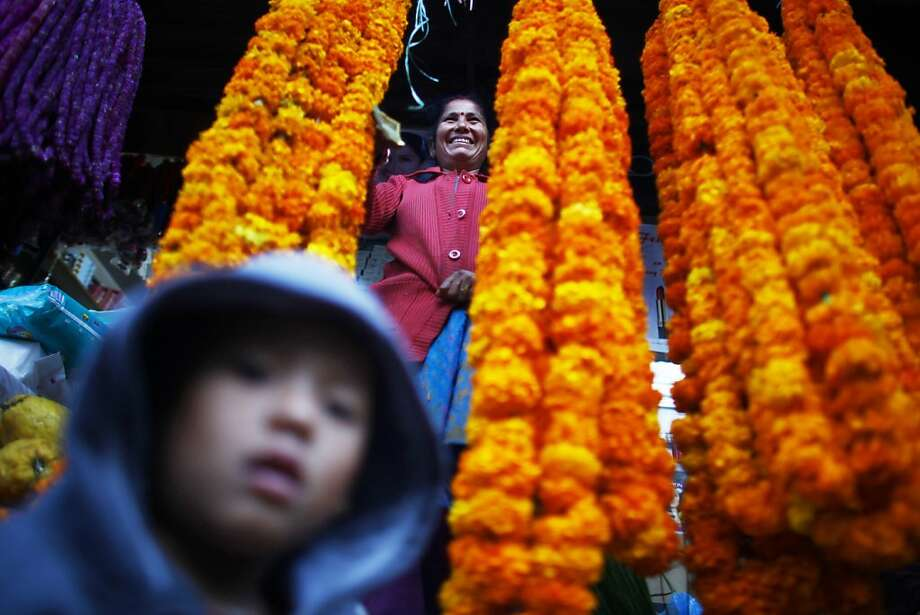 A flower vendor woman smiles as she waits for the customer during Tihar festival in Katmandu, Nepal, Monday, Nov 12, 2012. Tihar, the festival of lights is one of the most important of all Hindu festival, where they worship Goddess Laxmi, the Goddess of wealth and decorated their houses with oil lamps. The five day festival starting from the thirteenth day of the waning moon in October also meant for life and prosperity. Photo: Niranjan Shrestha, Associated Press