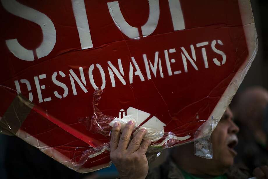 "A demonstrator holds a banner calling to ""Stop Evictions"" during a protest in front of the conservative party PP in Barcelona, Spain, Monday, Nov. 12, 2012.  Spanish officials are opening talks aimed at creating new regulations governing the eviction of indebted homeowners, after the suicide of two people about to suffer that fate shocked the nation. Photo: Emilio Morenatti, Associated Press"