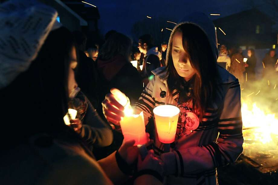 Joy Sulez, 18, of Nampa, Idaho, left, and Biamka Angel, 19, of Nampa, right, light their candles at the Monday, Nov. 12, 2012 candlelight vigil for their friend McQuen Forbush, a Marine who died this weekend from apparent carbon monoxide poisoning while on leave in Meridian, Idaho. Photo: Greg Kreller, Associated Press