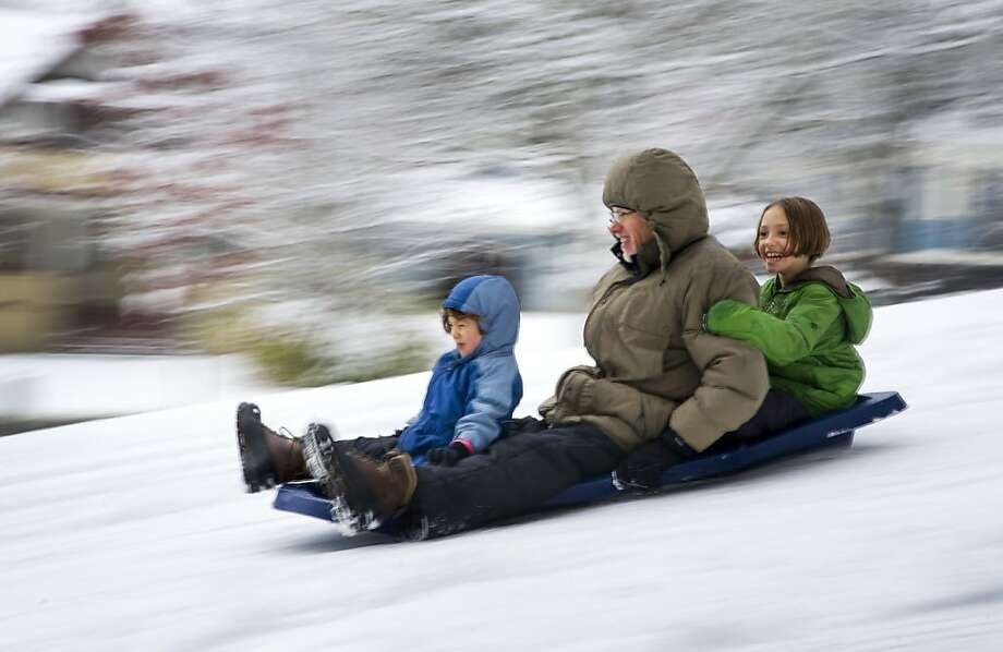 With several inches of fresh snow on the ground, Rob Roose and his daughters Lena, age 5, front, and Robin, age 10, in back, sled down Manito Hill in Manito Park, Monday, Nov. 12, 2012, in Spokane, Wash. Photo: Colin Mulvany, Associated Press